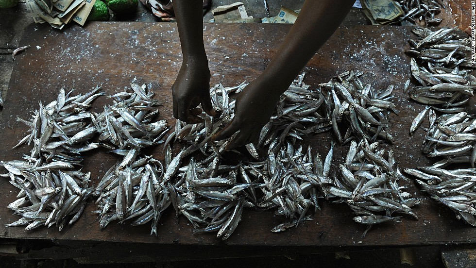 A Congolese woman arranges fish into clusters to sell at her stand in the southeastern Kivu province.