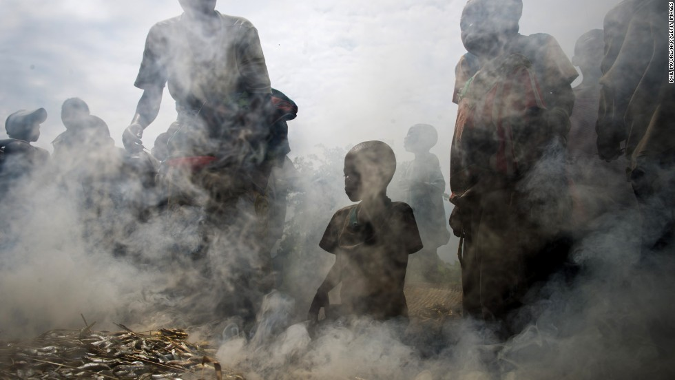 A group of Congolese gather around fish being smoked in the Mugunga camp near Goma.
