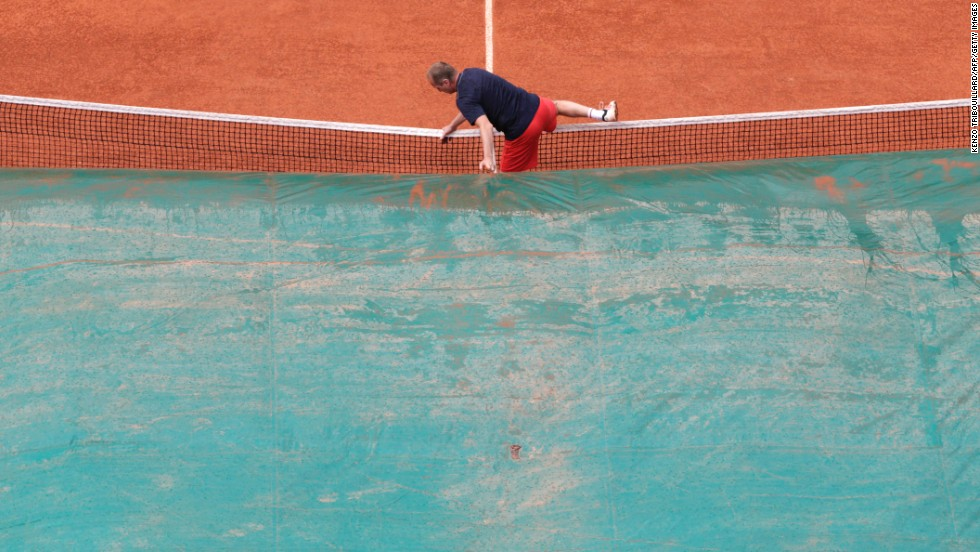 A court attendant covers the center court as rain falls over the Roland Garros stadium on June 6. The rain interrupted the semifinal match between Maria Sharapova and Victoria Azarenka.