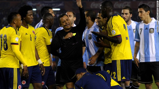 Referee Marlon Escalante battles to keep order between the Argentina and Colombia players in a stormy encounter.