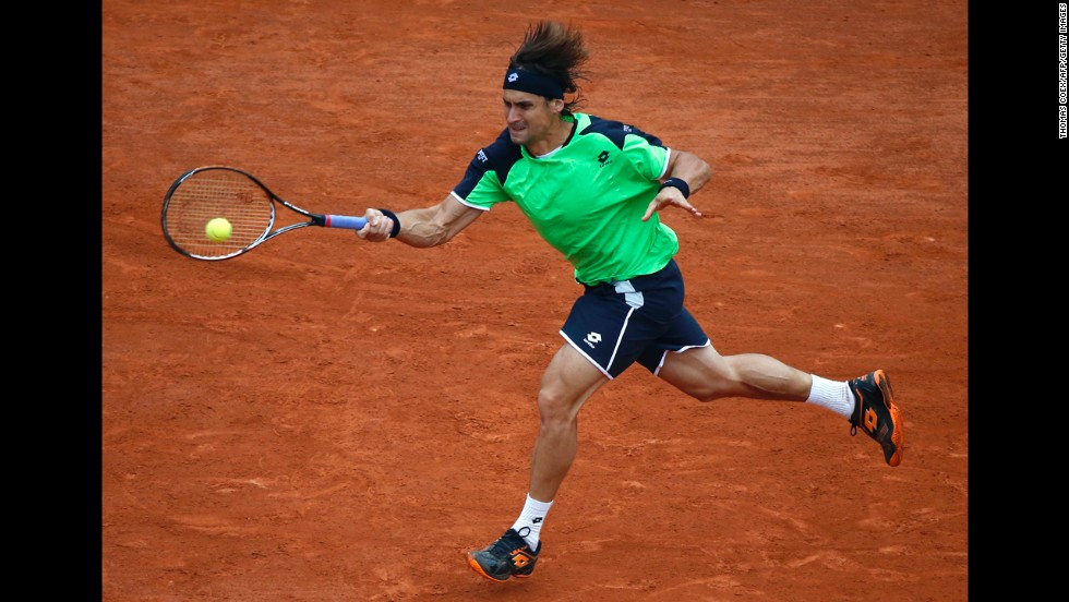 Ferrer returns a shot to Nadal.