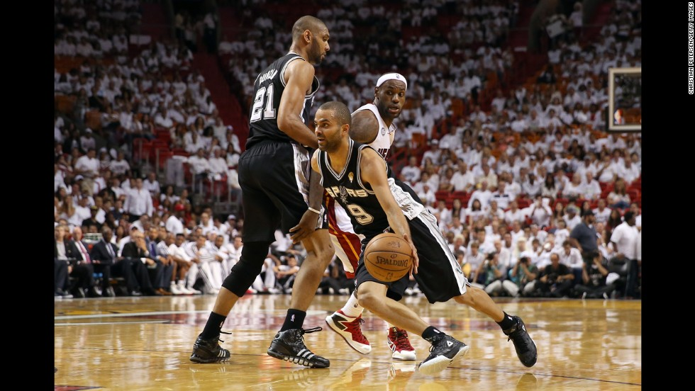 Tony Parker of the San Antonio Spurs uses a screen from Tim Duncan to get around LeBron James of the Miami Heat in the third quarter.