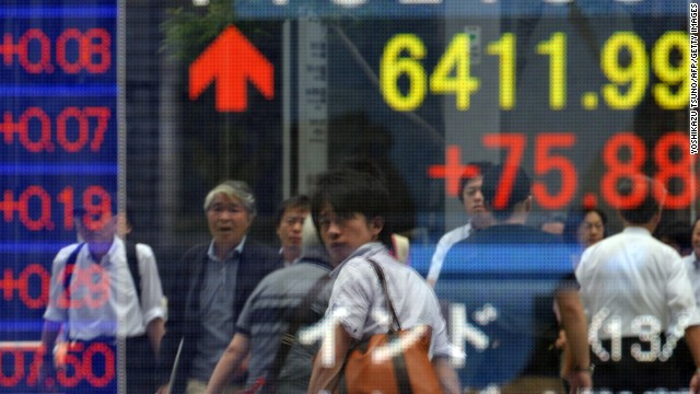 Tokyo pedestrians walk by the Nikkei Stock Exchange sign in June.
