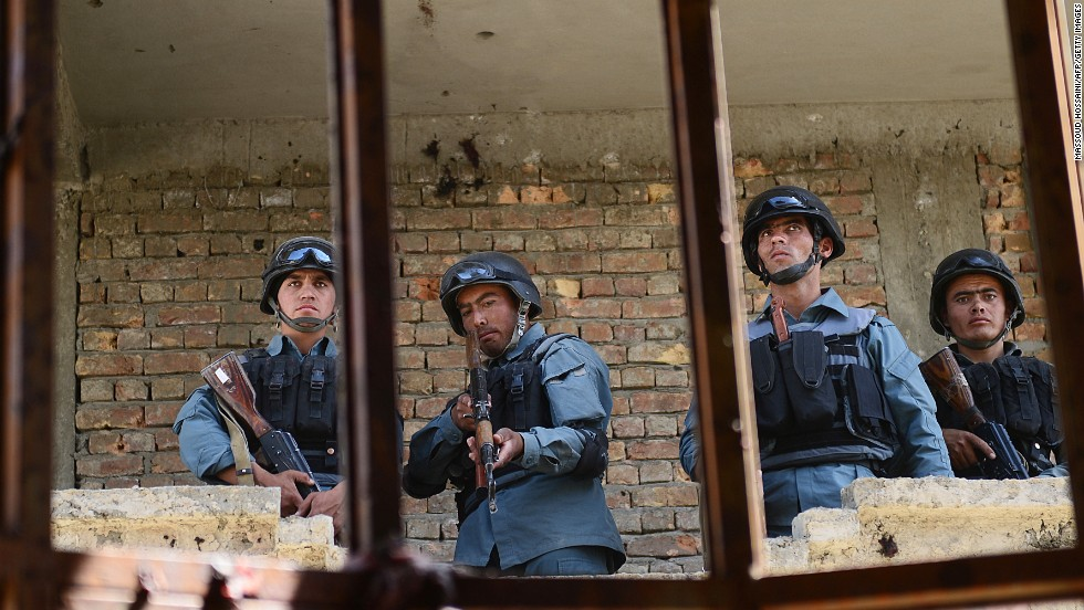 Afghanistan police stand guard in a building that was used for the June 10 attack near the Kabul airport.