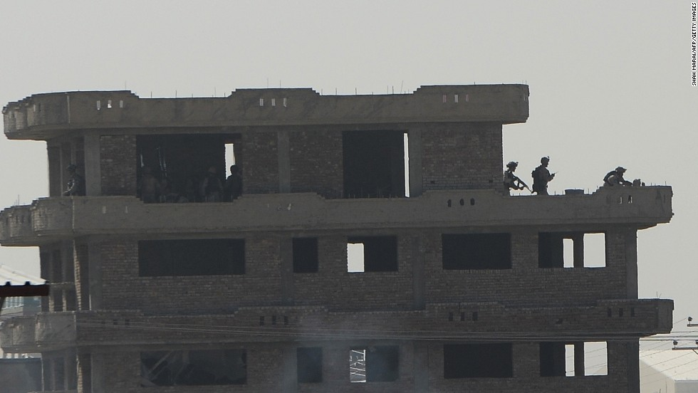 Members of the Afghan Crisis Response Unit run on top of a roof during the June 10 clash with Taliban fighters.