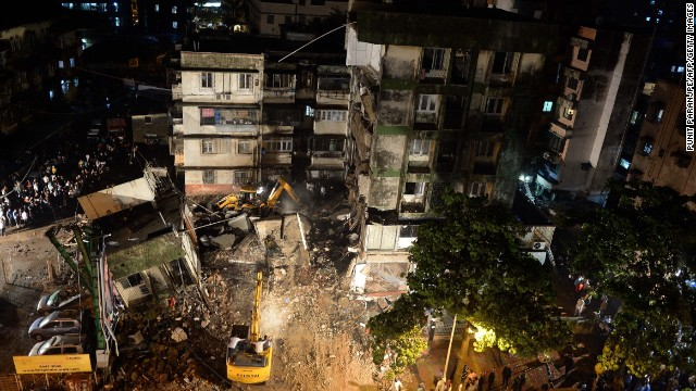 Excavators clear debris as rescue workers look for trapped people after a residential building collapsed in Mumbai on Monday.