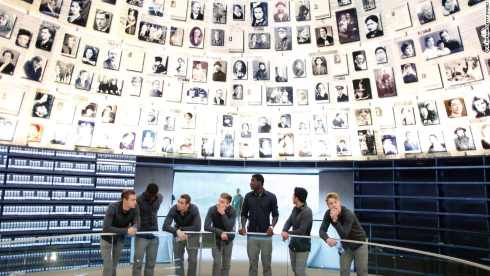 The players take a moment to pause and reflect while surrounded by photos of those who were murdered in the Holocaust.