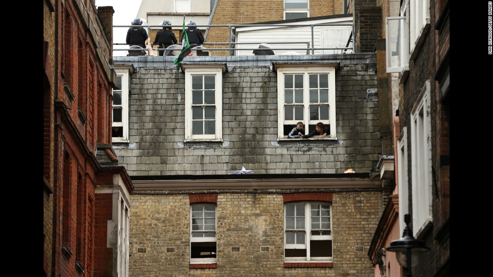 Activists look through windows as police stand guard on the rooftop on June 11.