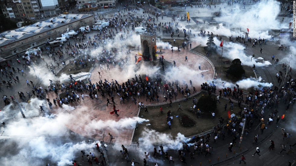 People flee as riot police fire tear gas on Taksim Square on June 11.