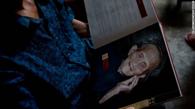 A relative of Luo Meizhen, claimed to be 127, holds her portrait.