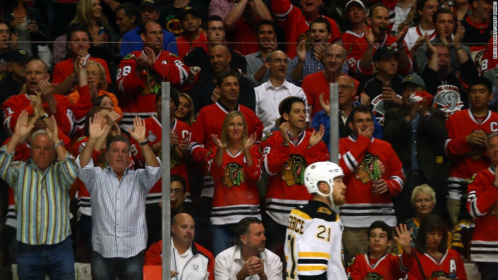 Chicago Blackhawks fans cheer for their team as Andrew Ference of the Boston Bruins skates by.
