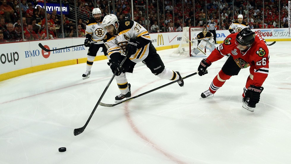 Patrice Bergeron of the Boston Bruins skates after the puck against Michal Handzus of the Chicago Blackhawks.