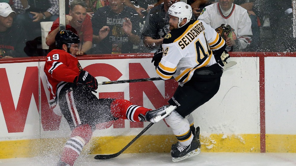 Jonathan Toews of the Chicago Blackhawks crashes into the boards next to Dennis Seidenberg of the Boston Bruins.