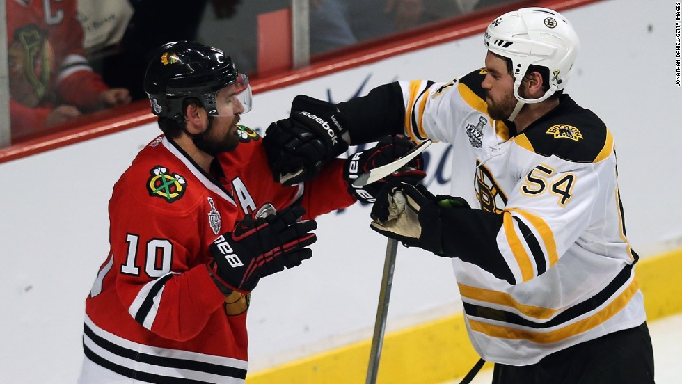 Patrick Sharp of the Chicago Blackhawks and Adam McQuaid of the Boston Bruins shove each other.