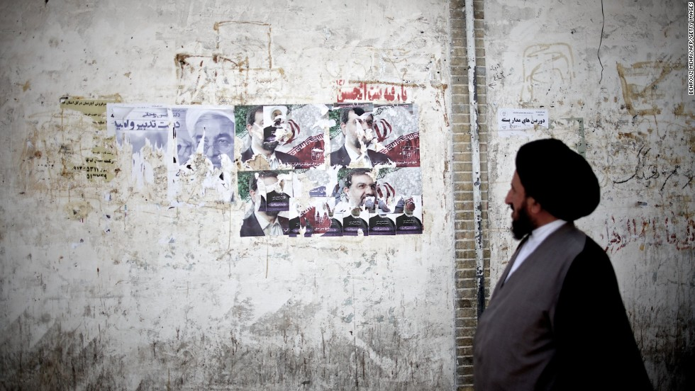 An Iranian clergyman walks past campaign posters on June 9 in Qom, south of the capital city of Tehran.