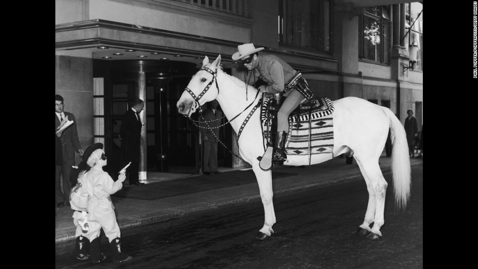 Outside the Savoy Hotel in London, two small boys hold up the Lone Ranger on July 21, 1958. Clayton Moore was in London for a four-week promotional tour, and the boys were  members of the Lone Ranger Club.