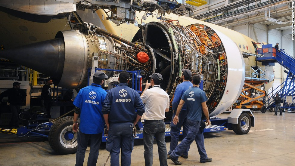 Technicians look at a Rolls-Royce jet engine, provided by UTC Aerospace Systems (formerly known as Goodrich), as they work on an A350-900 Airbus plane at the European aircraft maker's production plant in Toulouse.