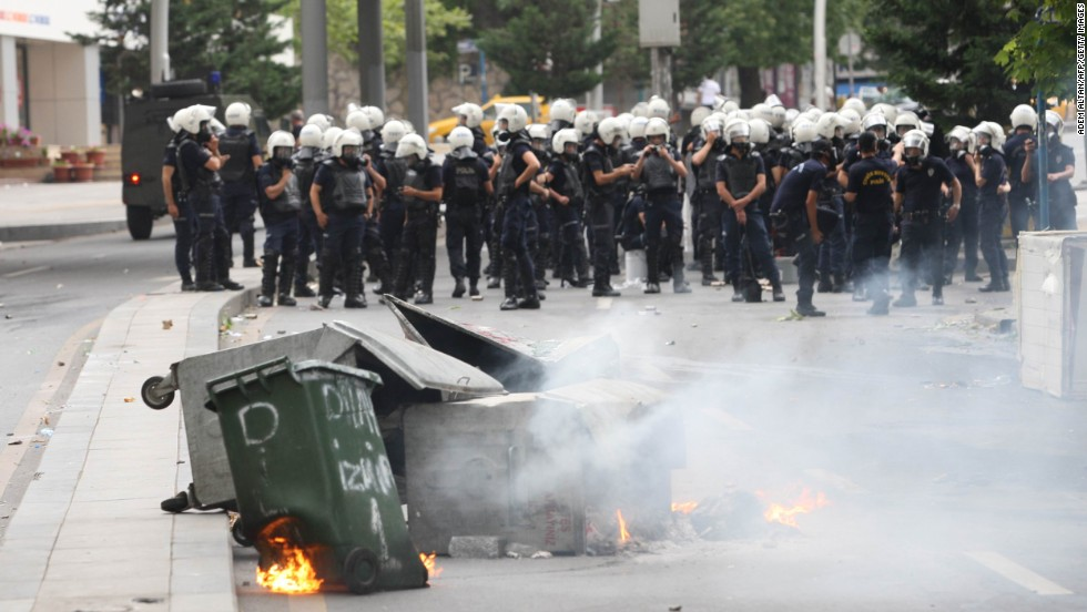 Trash containers burn in front of riot police forces in Ankara, Turkey, on June 16.
