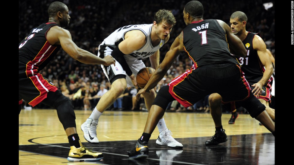 Tiago Splitter of the San Antonio Spurs runs into tight defense from Dwyane Wade, Chris Bosh and Shane Battier of of the Miami Heat.