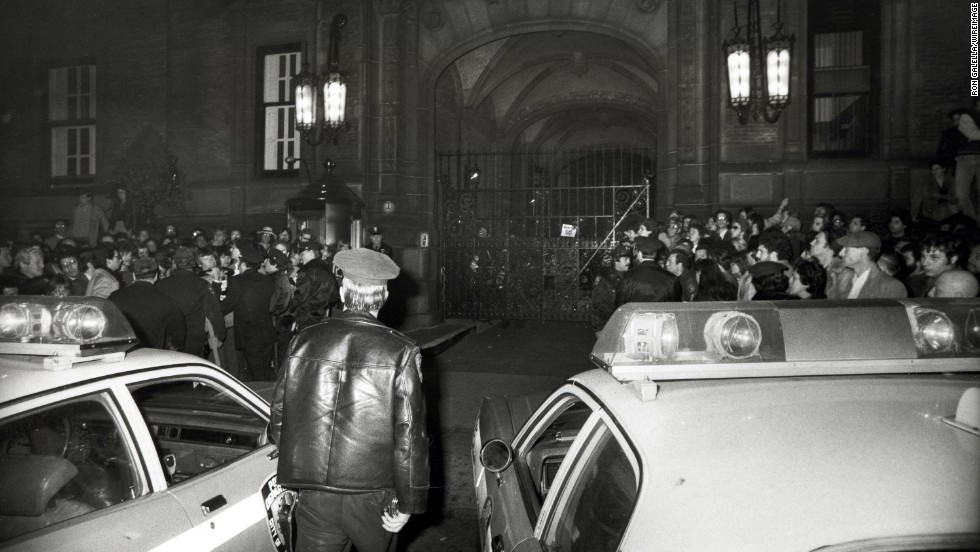 Crowds gather outside of the Central Park West apartment building, the Dakota, after news of Lennon's death.