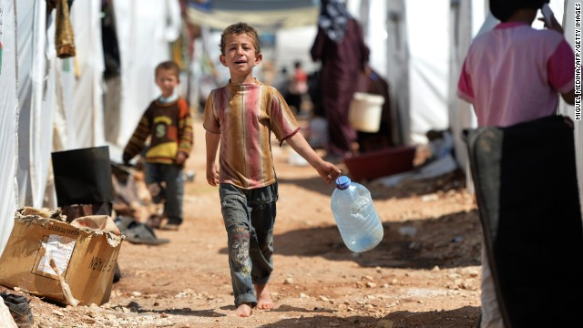 A young boy carries a jug for water at the Maliber al-Salam refugee camp on April 28.  The camp, located near the Turkish boarder, houses internally displaced Syrian families.