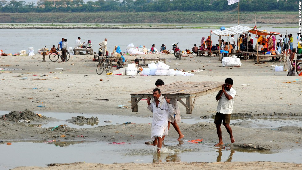 Hindu priests move their shelters from the banks of the Ganga river as the water level rises in Allahabad, Uttar Pradesh state, on June 19.