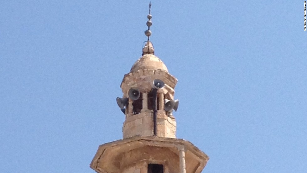 The mosque's minaret has a gaping hole after being hit by a shell.