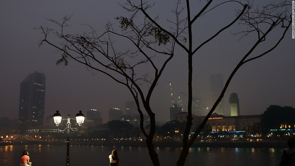 People sat by the Singapore River as the city's hazy skyline was relatively brightened by night lights on June 20.