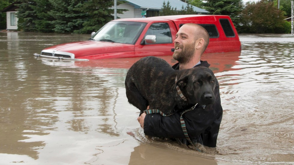 A man carries his dog to safety in High River, Alberta, on June 20.