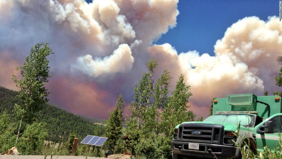 The West Fork Fire Complex burns 15 miles north of Pagosa Springs, on June 20, as a fire crew truck is parked nearby.