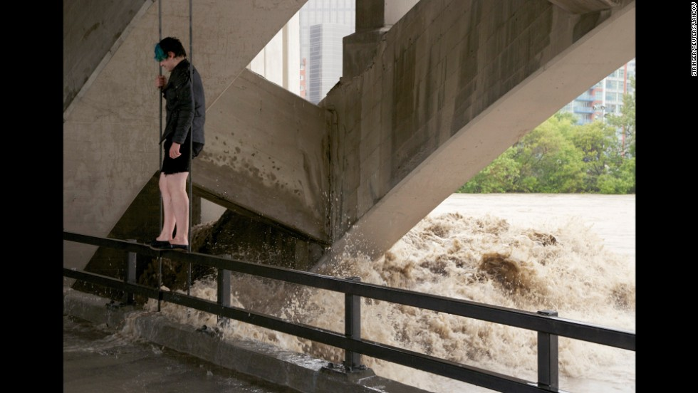 A man stands on a railing under Calgary's Centre Street Bridge as floodwater flows in the background on June 21.