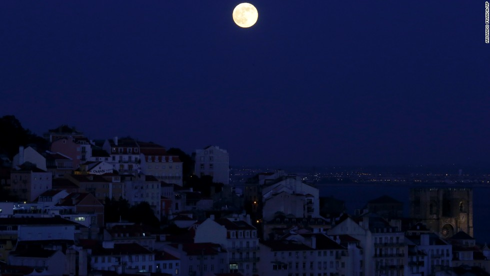 The full moon rises over Lisbon, Portugal, on June 23.