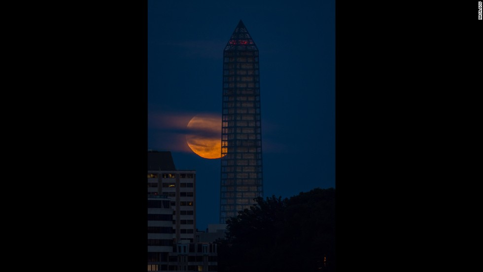 The moon rises behind the Washington Monument on June 23.