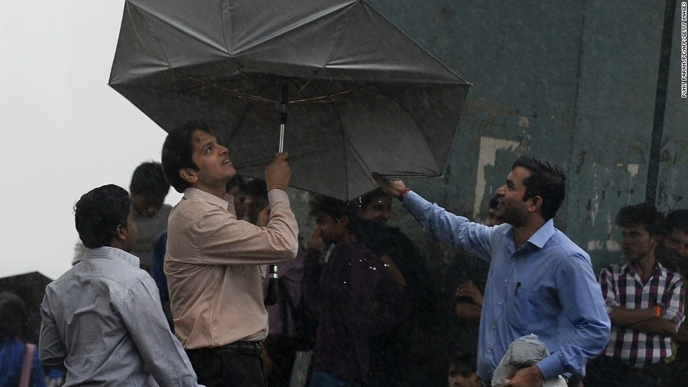 A man struggles with his umbrella during heavy rain in Mumbai on June 24.