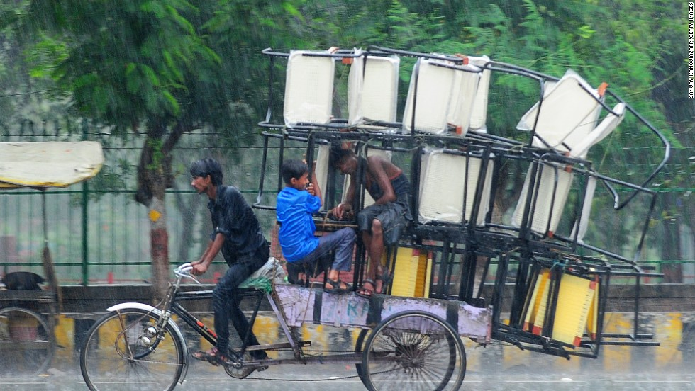 A rickshaw driver bikes through heavy rain in Allahabad, Uttar Pradesh state, on June 24.