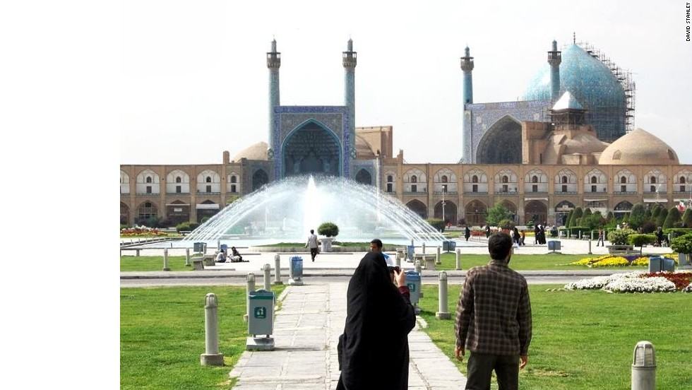 A couple crosses Naqsh-e Jahan Imam Square toward the Masjed-e Shah in Isfahan, Iran. Imam Square is the second largest city square in the world, surpassed only by Tiananmen in Beijing.