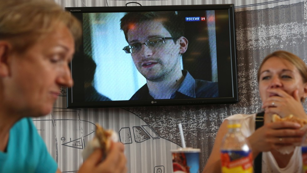 Transit passengers at Sheremetyevo airport in Moscow eat at a cafe: Edward Snowden is seen on a TV screen in the background.