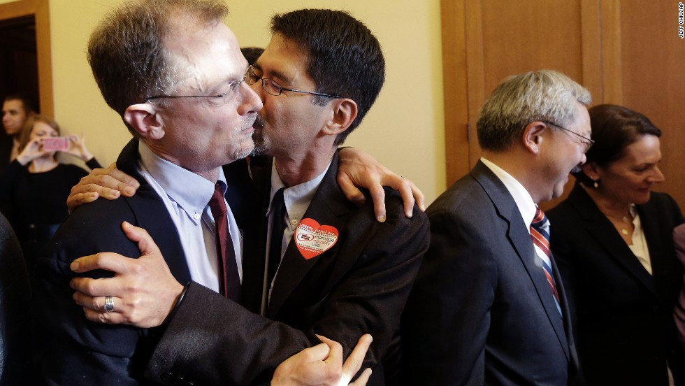 John Lewis, left, gets a kiss from his partner Stuart Gaffney at City Hall in San Francisco.