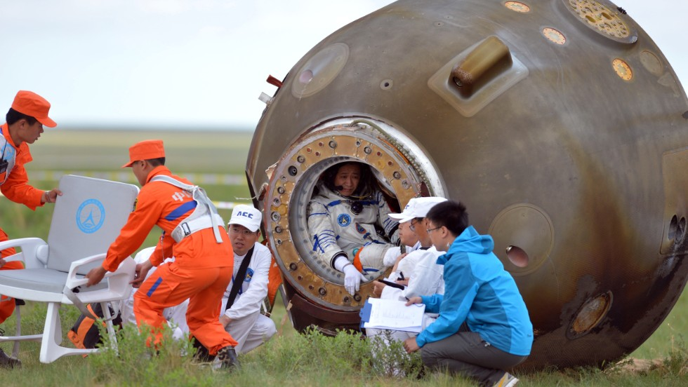 Nie Haisheng (4th R) sits inside the return capsule of the Shenzhou 10 spacecraft that landed after a 15-day mission in space -- China's longest manned space mission.