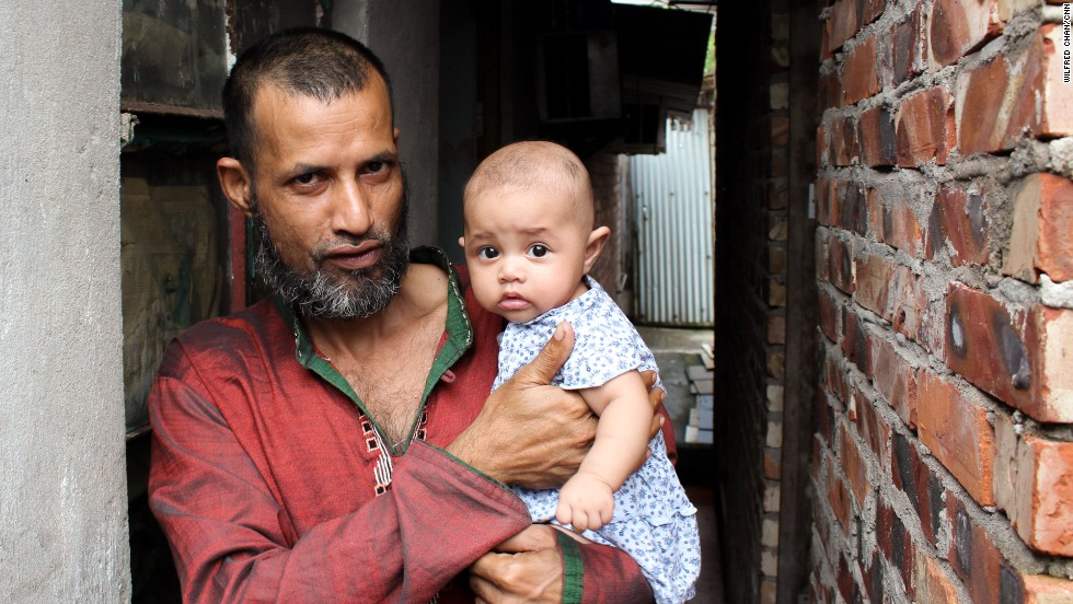 Mojibor, a 42-year old refugee from Bangladesh, holds his four-month old child in the village of Ping Che, Hong Kong on June 25, 2013. Mojibor and other asylum seekers in Hong Kong are legally forbidden to work, and dwell for years in decrepit housing on meager aid while awaiting a determination on their refugee status.