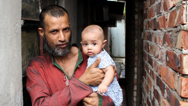 Mojibor, a 42-year old refugee from Bangladesh, holds his four-month old child in the slum village of Ping Che, Hong Kong on June 25, 2013. Mojibor and other asylum seekers in Hong Kong are legally forbidden to work, and dwell for years in decrepit housing on meager aid while awaiting a determination on their refugee status.