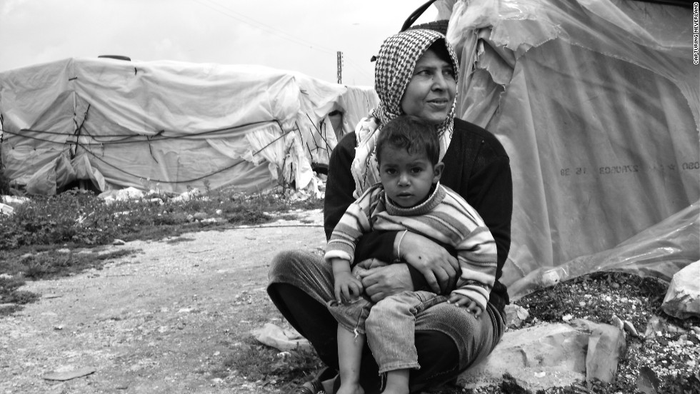 "This photo titled ""A Mother's Affection"" was taken by a 10-year-old child in a Lebanese village. It depicts a mother and her shoeless child. Looking concerned, or perhaps distraught, her arms are wrapped securely around the waist of the boy, who appears to be confused by the young photographer in front of him."