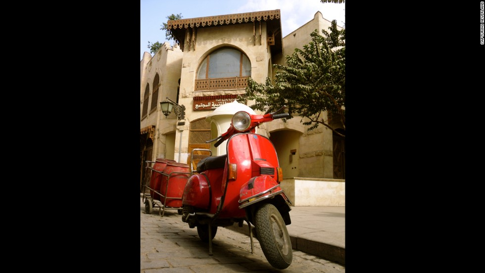 "A vibrant red scooter contrasts with the bleak background in this photo titled ""The Launch"" taken by an 8-year-old named Basma in Cairo, Egypt."
