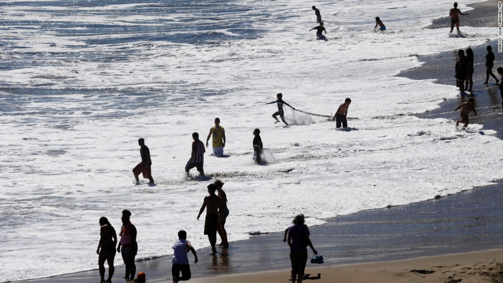 Beach-goers enjoy the surf at Natural Bridges in Santa Cruz on June 27.