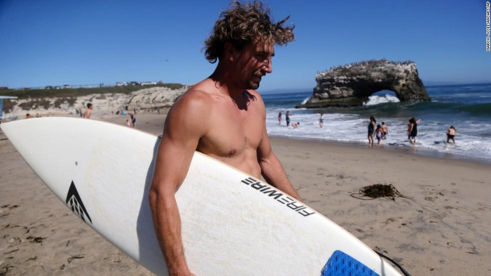 A surfer walks to the water at Natural Bridges in Santa Cruz on June 27.