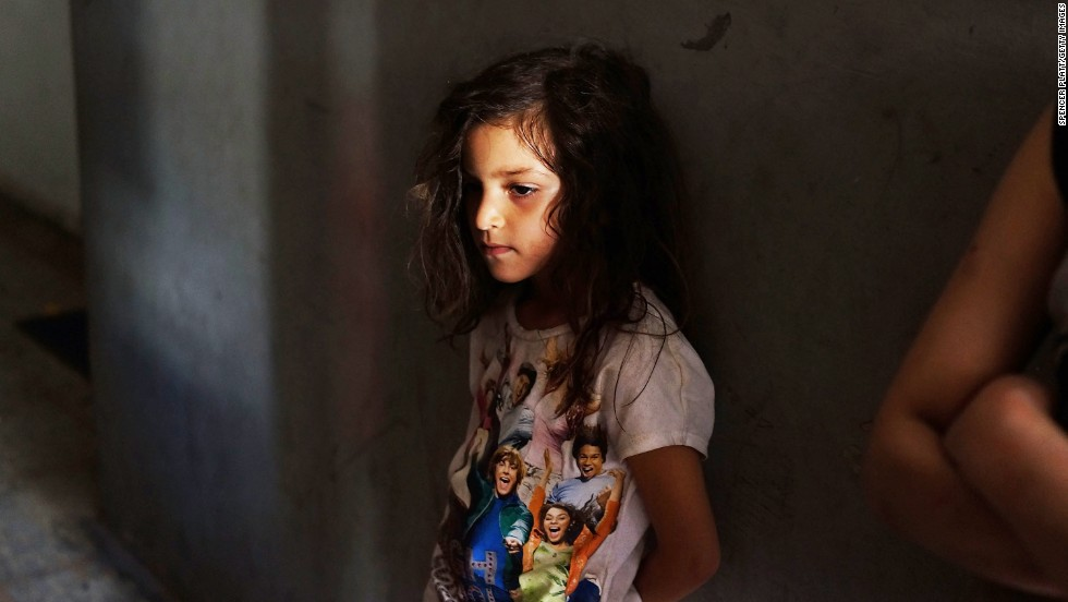 "JUNE 28 - BEIRUT, LEBANON: A Syrian girl stands in the entrance to the apartment she shares with other <a href=""http://cnn.com/2013/06/21/world/meast/syria-refugees-angelina-jolie"">Syrian refugees</a> in a poor neighborhood with a high concentration of refugees on June 27. <a href=""http://amanpour.blogs.cnn.com/category/lebanon/"">More than one million Syrians</a> have already fled to Lebanon, which is bracing for a million more."