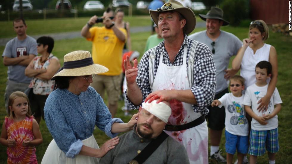 Spectators watch as reenactors portray medical treatment at a Confederate field hospital at the Daniel Lady Farm in Gettysburg.