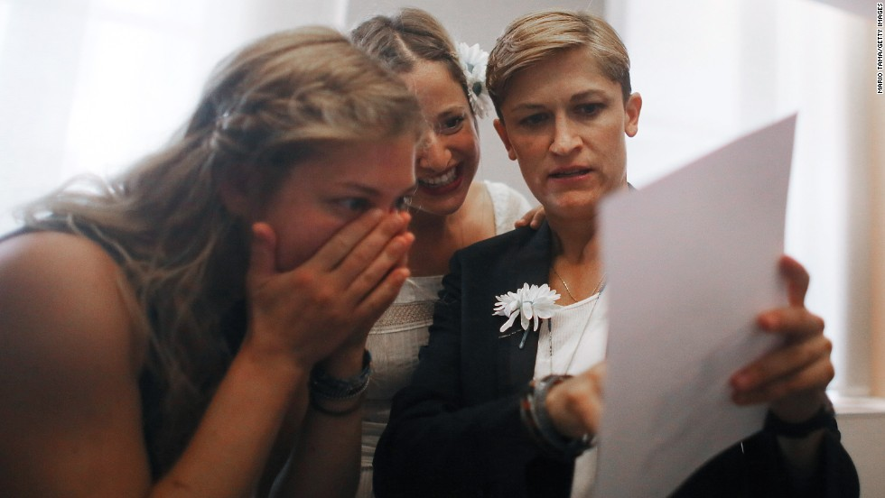 Stefanie Berks, center, and Daisy Boyd, right, view their marriage certificate with a friend after their ceremony in the east chapel at the Manhattan Marriage Bureau on June 28.