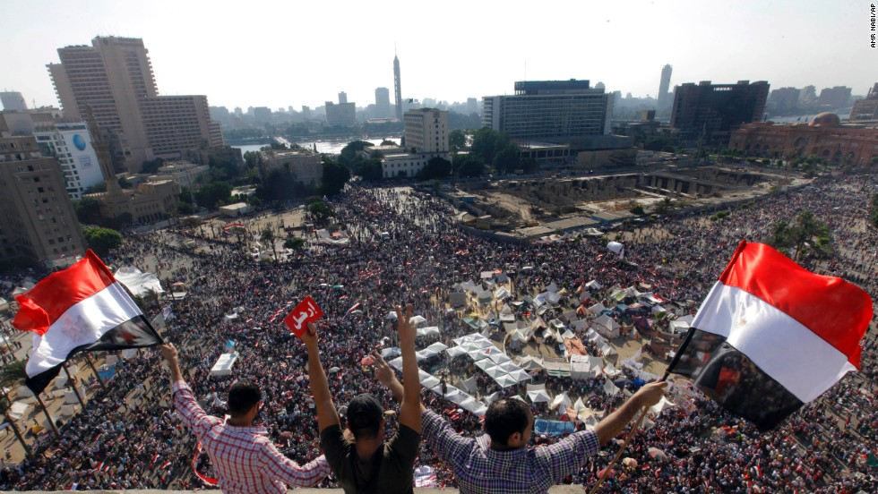 "Protesters wave national flags and a red card in Arabic reading ""leave"" in Tahrir Square during the June 30 demonstrations against Morsy."
