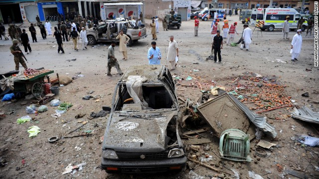 Security personnel and bystanders are pictured at the site of a bomb attack in Bedhber, Pakistan, on Sunday.